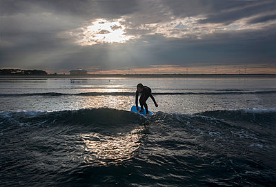 A Boy Surfs At Nahant Beach In Nahant, Massachusetts - p343m1416082 by Laurie Swope