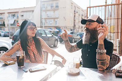 Mature hipster couple chatting at sidewalk cafe, Valencia, Spain - p429m1557451 by Eugenio Marongiu