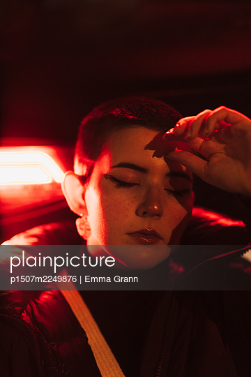 Young woman in red light, portrait - p1507m2249876 by Emma Grann