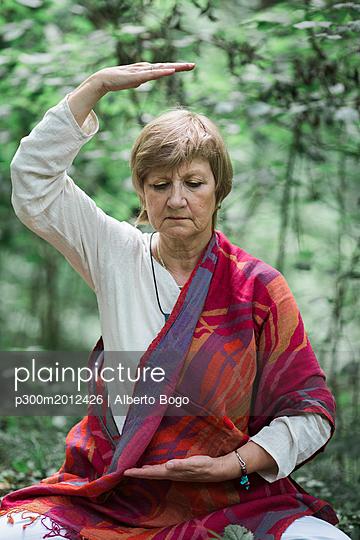 Senior woman doing yoga, meditating - p300m2012426 von Alberto Bogo
