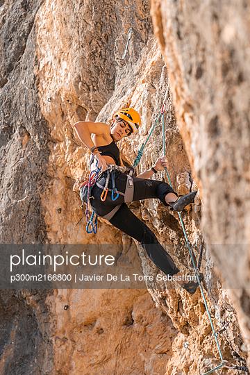 Woman climbing at rock face - p300m2166800 by Javier De La Torre Sebastian