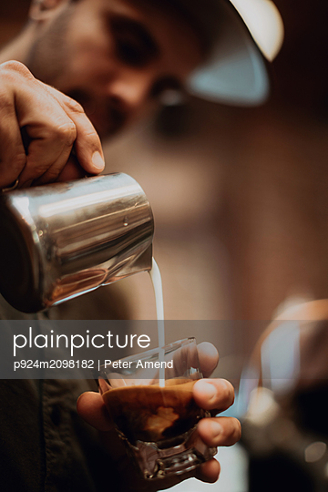 Barista pouring milk into coffee glass in cafe, close up of hands - p924m2098182 by Peter Amend