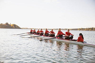 Rowing team in scull on sunny river - p1192m1016572f by Hero Images