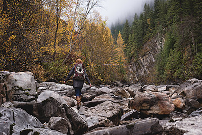 Rear view of woman walking on the rocks in autumn forest - p1315m1565217 by Wavebreak