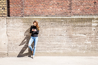 Woman with leaning against wall using cell phone - p300m2005633 von Jo Kirchherr