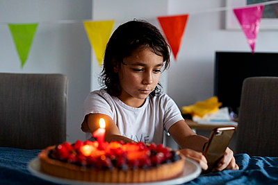 Portrait of serious boy with birthday cake at home looking at cell phone - p300m2189226 by Valentina Barreto
