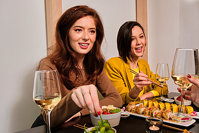 Female friends talking while having sushi dinner at restaurant - p300m2264628 by Antonio Ovejero Diaz