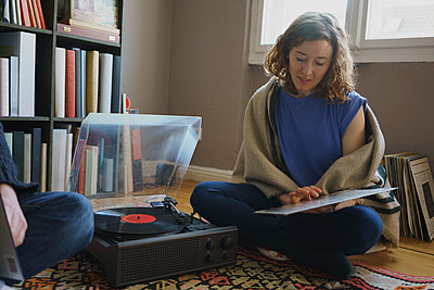 Woman sitting with record by turntable and man on carpet at home - p301m1579772 by Halfdark