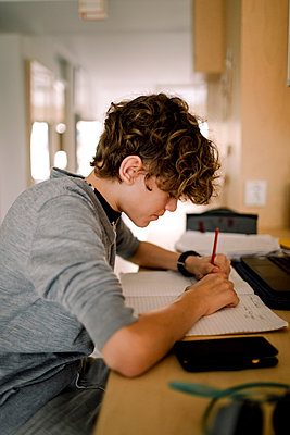 Boy writing in book while doing homework sitting at table - p426m2279655 by Maskot