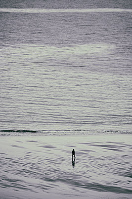 Man walking on beach at low tide - p597m2150402 by Tim Robinson