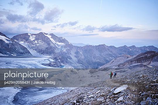 Hiker friends looking at glacier, Mont Cervin, Matterhorn, Valais, Switzerland - p429m2058431 by Jakob Helbig