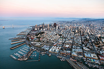 Aerial view of cityscape by sea against sky during sunset - p1166m1230532 by Cavan Images