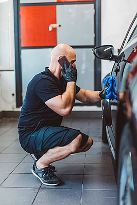 Side view of male worker talking on smart phone while cleaning car with towel in workshop - p1166m2060383 by Cavan Images