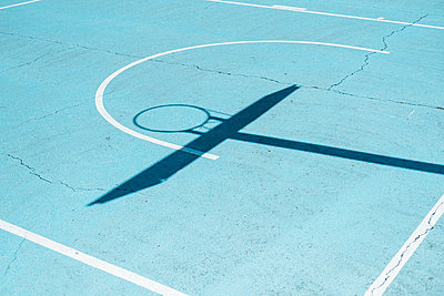 Shadow of a basketball hoop on colorful court - p1166m2136207 by Cavan Images