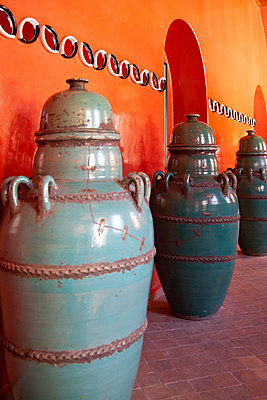 Ceramic Urns Against Orange Wall - p1248m2109276 by miguel sobreira