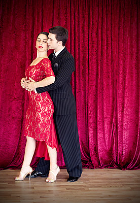 Tango dancers against red curtain - p1445m2128305 by Eugenia Kyriakopoulou