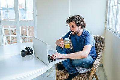 Man drinking vegetable juice while using laptop at home - p300m1459781 by Kiko Jimenez