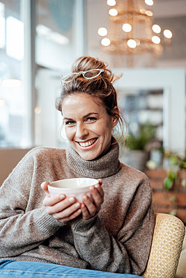Woman smiling while holding drink bowl in coffee shop - p300m2282257 by Joseffson