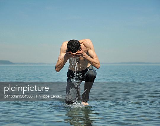 Mann mit nacktem Oberkörper planscht im Wasser - p1468m1584963 von Philippe Leroux