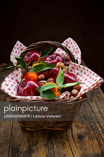 Wickerbasket of red apples, tangerines, hazelnuts and walnuts - p300m2080878 by Larissa Veronesi