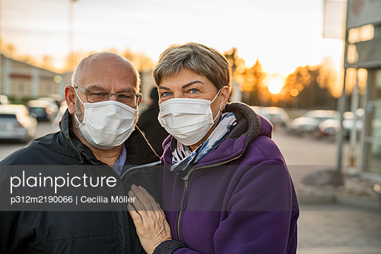 Couple wearing protective mask looking at camera - p312m2190066 by Cecilia Möller