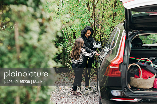 Mid adult woman teaching daughter to charge electric car at charging station - p426m2195239 by Maskot