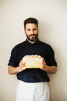 Baker holding a loaf of freshly baked white bread. - p1100m1158399 by Mint Images