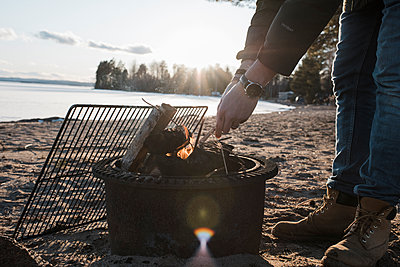 man's hands lighting a bonfire outside on a beach in Sweden - p1166m2171473 by Cavan Images