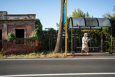 Woman waiting at bus stop - p1437m2254414 by Achim Bunz