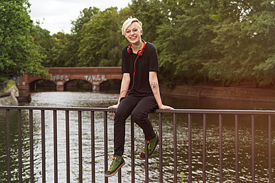 Laughing young woman sitting on railing in front of a canal - p300m1175961 by A. Tamboly
