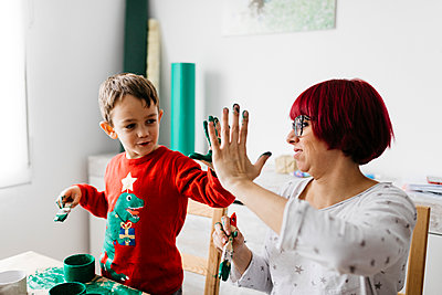 Happy mother and son high fiving while doing crafts at home - p300m2114526 von Josep Rovirosa