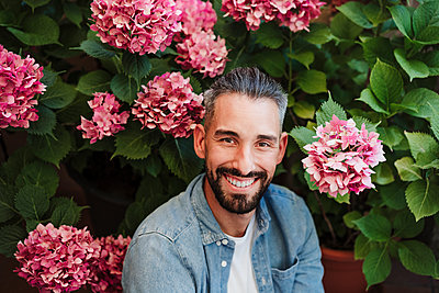 Smiling male freelancer sitting in front of hydrangea plant - p300m2293396 by Eva Blanco