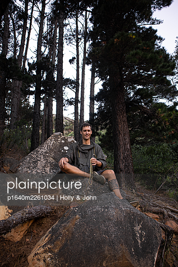 Hiker with prayer bead takes a break on a boulder - p1640m2261034 by Holly & John