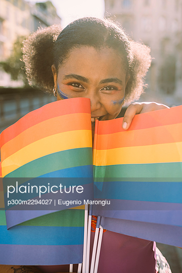 Smiling woman with rainbow flag on sunny day - p300m2294027 by Eugenio Marongiu