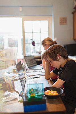 Boy homeschooling at laptop in dining room - p1023m2201044 by Paul Bradbury