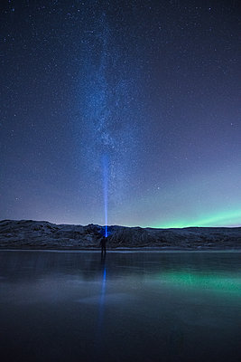 Mid distance view of hiker with flashlight by lake against star field at night - p1166m1543837 by Cavan Images