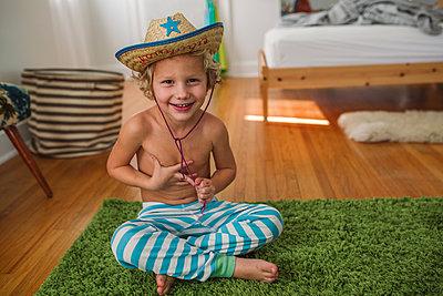 Junge mit Strohhut im Kinderzimmer - p1361m1225610 von Suzanne Gipson