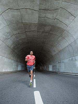 Black man running in urban tunnel - p555m1414880 by Erik Isakson