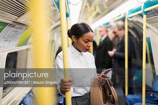UK, London, businesswoman in underground train looking at cell phone - p300m1581307 by Mauro Grigollo