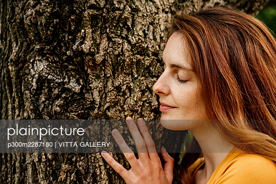 Smiling woman relaxing on tree trunk in garden - p300m2287180 by VITTA GALLERY