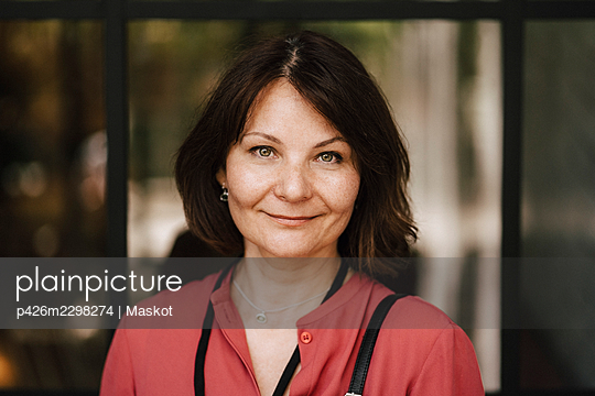 Portrait of smiling mature businesswoman standing at convention center - p426m2298274 by Maskot