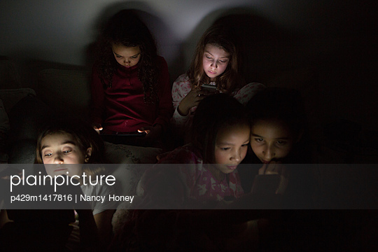 Girls in darkness at slumber party illuminated by digital tablet - p429m1417816 by Nancy Honey