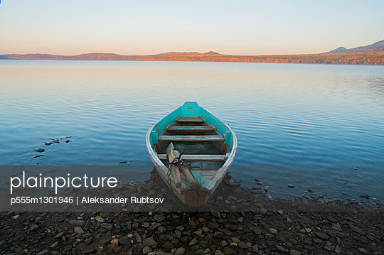 Empty rowboat on rocky shore of lake at sunset - p555m1301946 by Aleksander Rubtsov