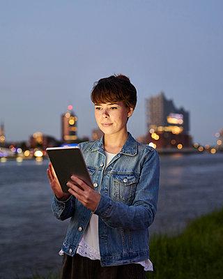 Frau mit Tablet gegenüber der Elbphilharmonie - p1124m1150192 von Willing-Holtz