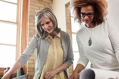 Multi-ethnic businesswomen examining blueprint in board room - p1166m1141470 by Cavan Images