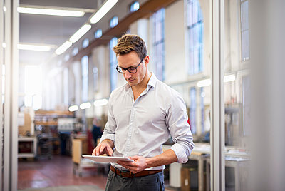 Young businessman in factory using tablet - p300m1562441 by Daniel Ingold