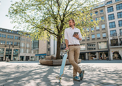 Businessman with tablet and skateboard in the city - p300m2198422 by Joseffson