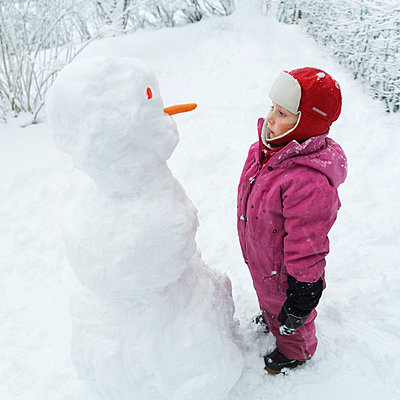 A girl and a snowman looking at eachother Sweden. - p31215964f by Susanne Walström