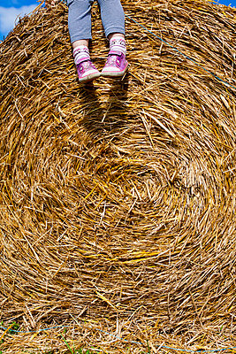 Girl on a bale of straw - p756m740363 by Bénédicte Lassalle