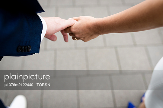 Couple holding hands - p1076m2122440 by TOBSN